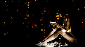 Woman on White Shoes Sitting With String Lights on Dim Light Room Stock Image