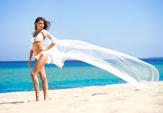A woman in white silk posing on the beach Stock Images