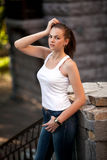 Woman in white singlet and jeans on street Royalty Free Stock Photo