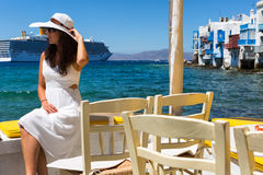 Woman in white sits at the waterfront of Little Venice in Mykonos. Elegant woman in white sits at the waterfront of Little Venice in Mykonos, Greece while cruise Stock Photography