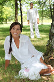 Woman in white sitting in park Stock Images