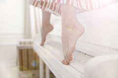 Woman sitting on a piano. A woman in white sitting on a piano with her feet on the piano keys Stock Photography