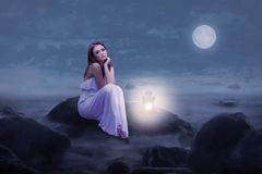 Woman in white sitting on rocks at night  Stock Images