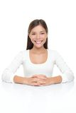 Woman in white sitting by table. Beautiful young woman smiling sitting by table. Serene Asian Caucasian woman in white isolated on white background Royalty Free Stock Photo