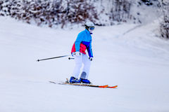 Woman in white skiing suit on mountain slope Royalty Free Stock Photography