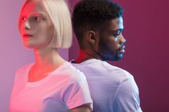 Woman with white skin and man with black skin standing back to back stock photo