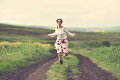 Woman in white skirt running on a countryside road Stock Image