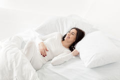Woman in white sleepwear awakening in bed at home. Attractive woman in white sleepwear awakening in bed at home Royalty Free Stock Photography