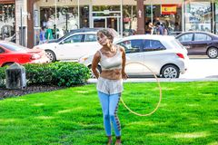 Woman in White Sleeveless Shirt and Blue Pants Holds Yellow Hula Hoop Stands on Green Grass Stock Photos