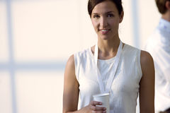 Woman in white sleeveless top holding disposable cup, smiling, front view, portrait Royalty Free Stock Photos