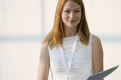 Woman in white sleeveless top holding folder, smiling, front view, portrait Royalty Free Stock Photos