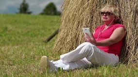 Woman with white smartphone sits near haystack and listening to music stock footage