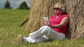 Woman with white smartphone sitting near haystack and listening to music stock footage