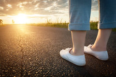 Woman in white sneakers standing on asphalt road towards sun. Travel, freedom concepts. Stock Photos