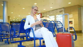 Woman in a white suit sitting in the waiting room with the phone. stock video footage