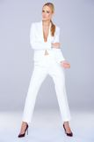 Woman in white suit standing confidently Royalty Free Stock Photos