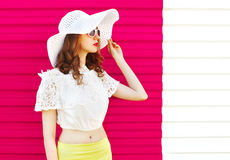 Woman in white summer straw hat looking over colorful pink Royalty Free Stock Image