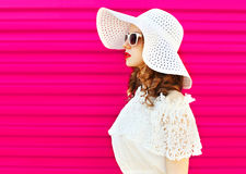 Woman in white summer straw hat over colorful pink background Stock Photography