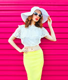 Woman in white summer straw hat and skirt over colorful pink Stock Photo