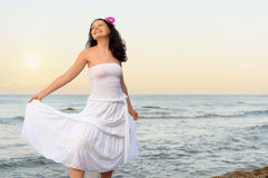 The woman in a white sundress on seacoast Stock Images