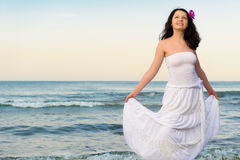 The woman in a white sundress on seacoast. Royalty Free Stock Image