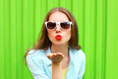Woman in white sunglasses sends an air kiss over colorful green Royalty Free Stock Photos