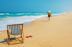 Woman  in white sunhat. Deckchair  and  woman  in white sunhat going along the beach .Vacation and travel concept Stock Photo