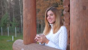 Woman In White Sweater With Cup Of Tea Is Goes On The Veranda Of A Wooden House. A young cheerful brunette woman, in a white warm sweater, walks to the veranda stock footage
