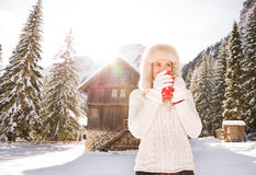 Woman in white sweater enjoying hot beverage near mountain house. Christmas season in relaxed style of contemporary countryside living. Young woman in white Royalty Free Stock Image
