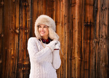 Woman in white sweater and furry hat near rustic wood wall Stock Images