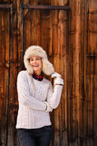 Woman in white sweater and furry hat near rustic wood wall Stock Image