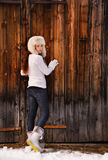 Woman in white sweater and furry hat posing near wood wall Stock Photography