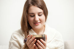 Woman in white sweater holding cup of tea Royalty Free Stock Photos