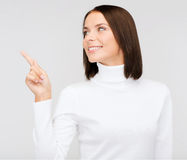 Woman in white sweater pointing to something Stock Images