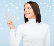 Woman in white sweater pointing to something Stock Image