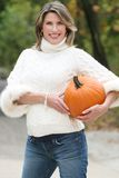 Woman in White Sweater with Pumpkin Stock Images