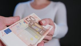 A Woman in White Sweater Receiving Cash. A women in a white sweater receiving cash Euros against a black background. Close-up shot Royalty Free Stock Image