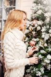 Woman in white sweater stands near a Christmas tree Royalty Free Stock Photography