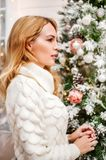 Woman in white sweater stands near a Christmas tree Stock Image