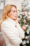 Woman in white sweater stands near a Christmas tree Royalty Free Stock Images