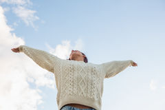 Woman in white sweater stretching her arms against sky Royalty Free Stock Photos