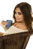 Woman in white sweater and tattoo sit blue mug look over shoulde Stock Image