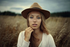 Woman in White Sweater Wearing Brown Cowboy Hat Beside Brown Grass during Daytime Royalty Free Stock Images
