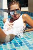 Woman in white swimsuit posing near swimming pool. Beautiful stylish tan girl. Summer day on island. Phuket, Thailand. Woman in white swimsuit posing near Royalty Free Stock Photo