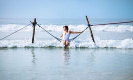 Woman in white swimsuit sits in hammock swing over the ocean sur. F line Stock Photography