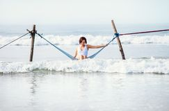 Woman in white swimsuit sits in hammock swing over the ocean sur Royalty Free Stock Photography