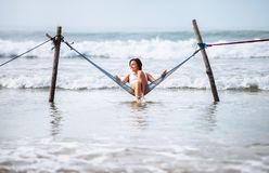 Woman in white swimsuit sits in hammock swing over the ocean wav. Es Royalty Free Stock Images