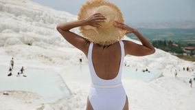 Woman in a white swimsuit and a straw hat stands on a white mountain. In Pamukkale stock footage