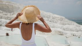 Woman in a white swimsuit and a straw hat stands on a white mountain. In Pamukkale stock video footage