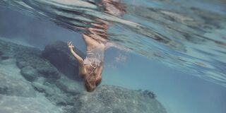 Woman in white swimsuit underwater